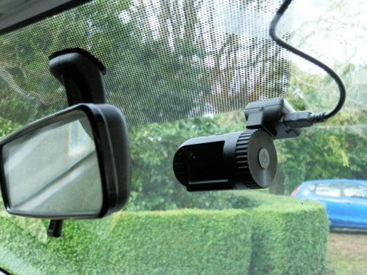 Dashcam behind rearview mirror in car